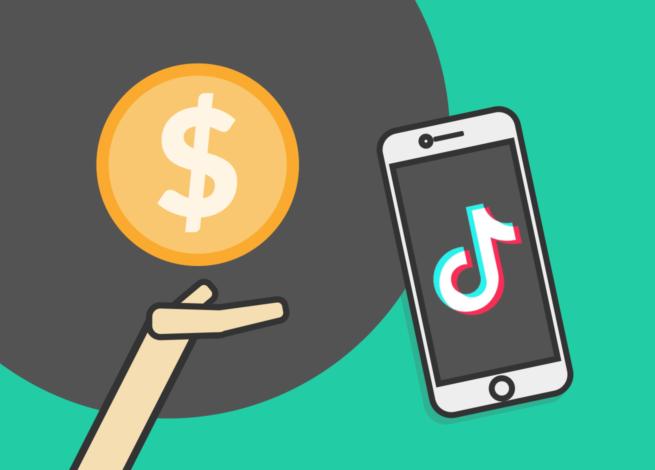 Una mano sostiene dinero apuntando a un celular con la app TikTok.