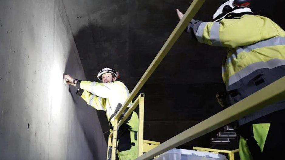 Dos personas instalan aparatos de Waze en túnel, bajo el concepto de Smart City.