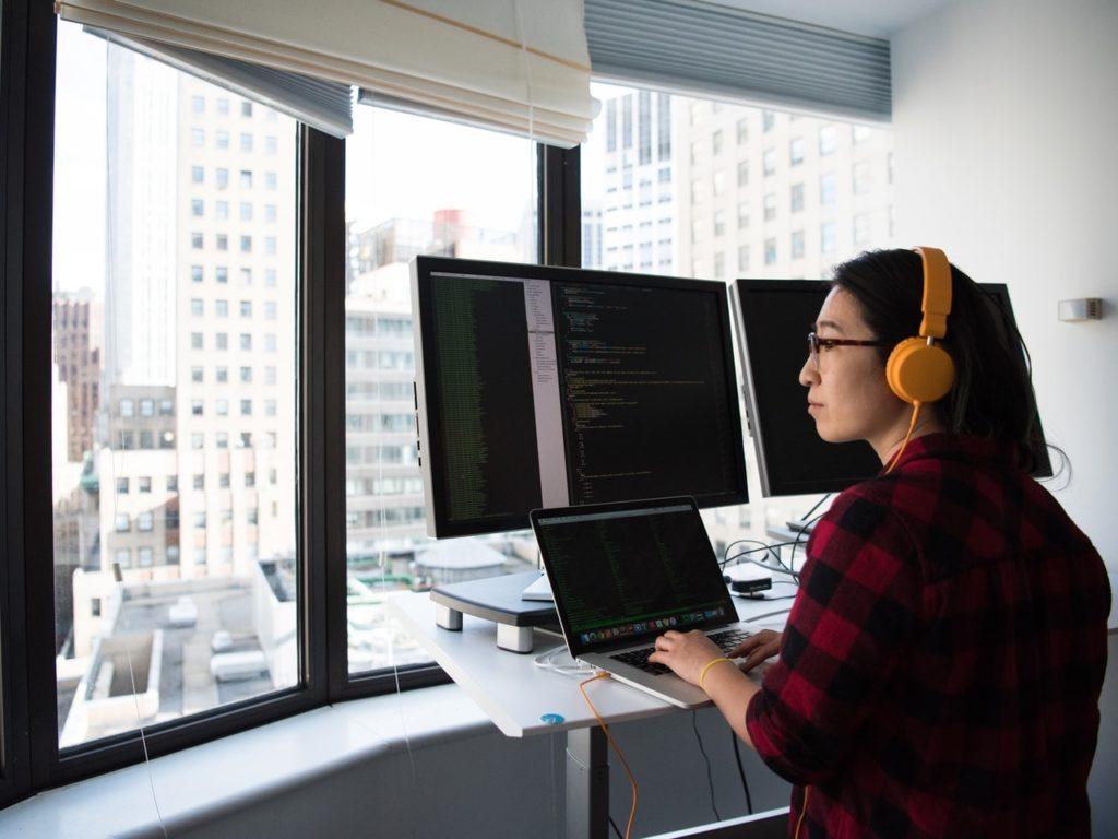 mujer frente a un computador y diversas pantallas.